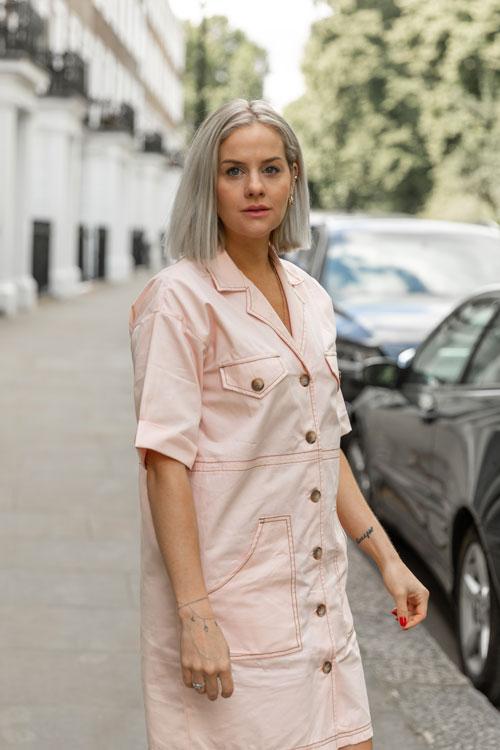 Eliza Rinaldi, mulher branca, magra, de cabelo chanel loiro platinado, olha para a câmera