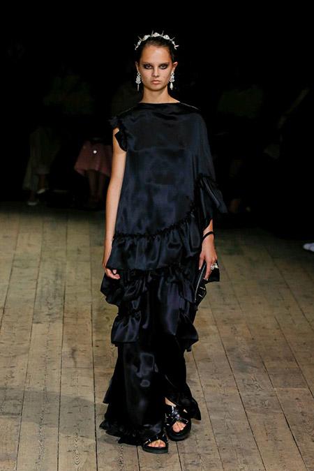 Desfile Simone Rocha na LFW Primavera / Verão 20, modelo usa vestido longo em cetim preto.