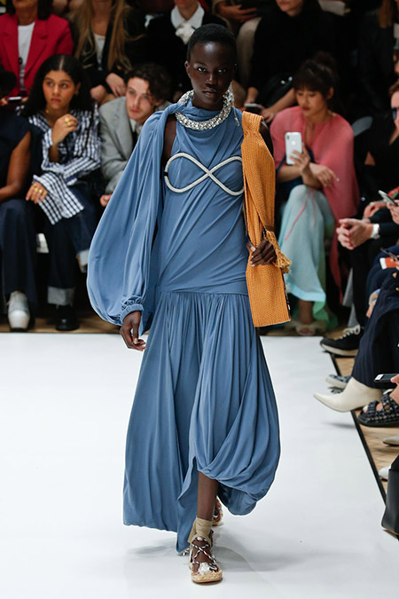Desfile JW Anderson na LFW Primavera / Verão 20, modelo usa vestido longo, bufante azul, com detalhe em 8 nos seios e gola com pedrarias.