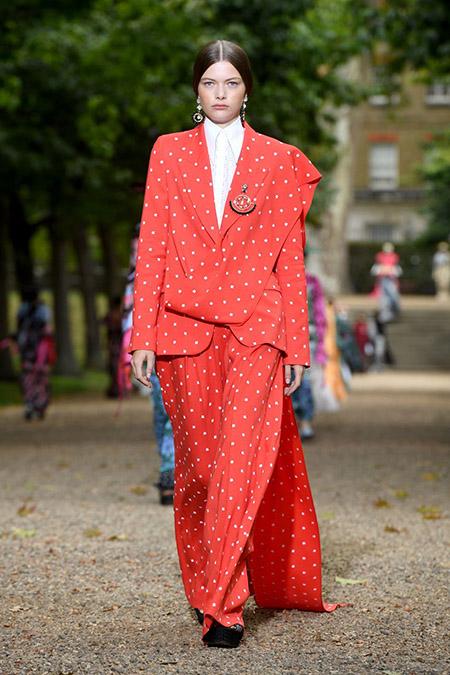Desfile da Erdem na LFW Primavera / Verão 20, modelo veste conjunto em vermelho com poás creme e camisa branca.