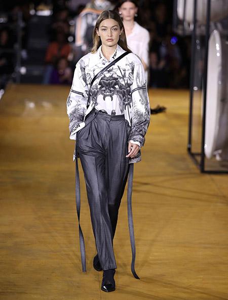 Desfile Burberry na LFW Primavera / Verão 20, Gigi Hadid veste camisa com estampas em preto e calça cinza chumbo.