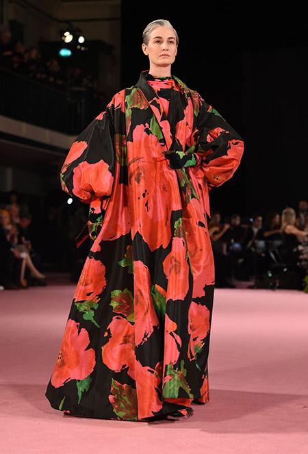 Desfile Richard Quinn na LFW Primavera / Verão 20, modelo Erin O'Connor usa vestido longo e amplo floral, com fundo preto e grandes flores vermelhas e folha verdes.