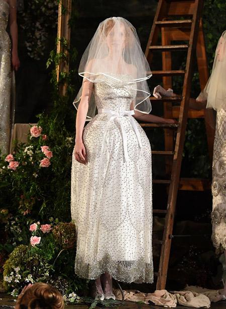 Desfile Richard Quinn na LFW Primavera / Verão 20, noiva com vestido off-white e bordado em pedrarias. O véu cobre seu rosto.