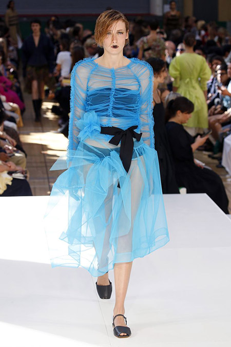 Desfile Molly Goddard na LFW Primavera / Verão 20, modelo veste vestido translúcido de tule azul, com top e calcinha pretas. Um laço preto amarra a cintura do vestido na frente.