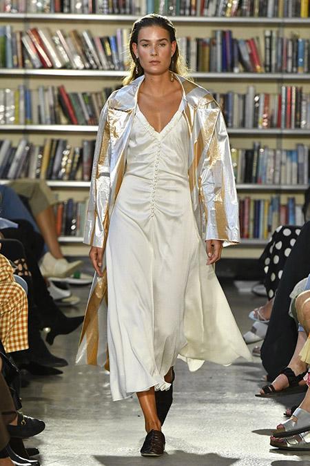 Desfile Rejina Pyo na LFW Primavera / Verão 20, modelo usa vestido em bege perolado midi, com botões pequenos da mesma cor na frente. Ela usa um trench coat metalizado com listras amarelo e branco.