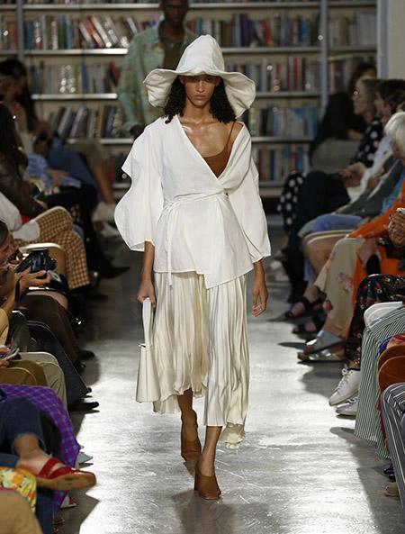 Desfile Rejina Pyo na LFW Primavera / Verão 20, modelo usa ampla blusa off white com amarração trespassada na frente. Saia bege, sapatos marrons e chapéu mole de ponta branco.