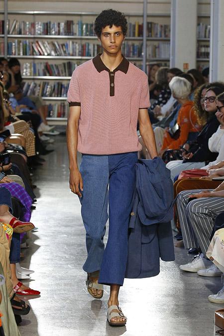 Desfile Rejina Pyo na LFW Primavera / Verão 20, modelo masculino usa jeans reto com uma perna mais escura e outra mais clara, camisa pólo rosa com detalhes em marrom.