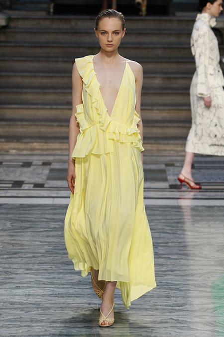 Desfile Victoria Beckham na LFW Primavera / Verão 20, modelo veste vestido midi com babados amarelo pastel.