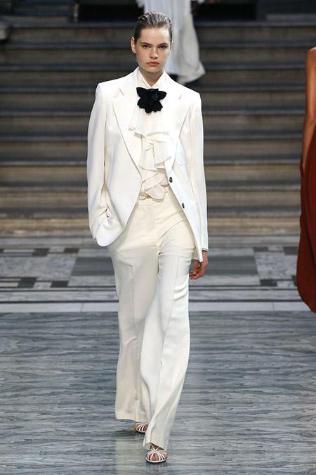 Desfile Victoria Beckham na LFW Primavera / Verão 20, modelo veste terno branco com camisa bufante branca e gravata em laço preta.