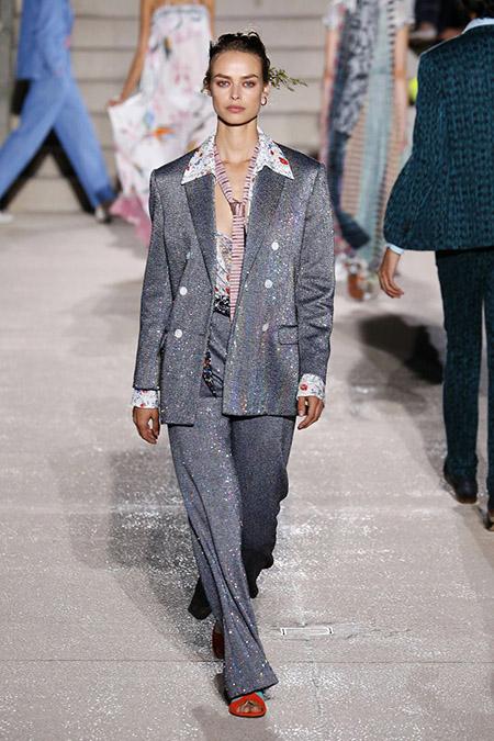 No desfile da Moschino da MFW Primavera / Verão 20, Cara Taylor veste paletó cinza com brilhos e camisa aberta e gravata listrada bem aberta.