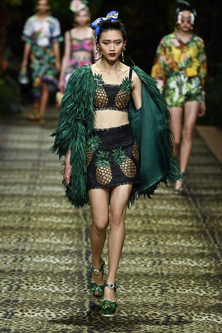 No desfile da Dolce e Gabanna da MFW Primavera / Verão 20, modelo veste saia e top com estampas de abacaxi e casaco de franjas verde.