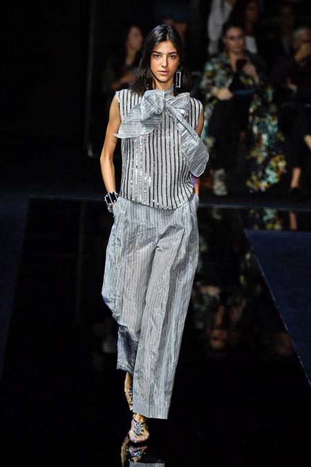 No desfile da Emporio Armani da MFW Primavera / Verão 20, modelo veste calça cinza clara com listras suaves verticais e blusa sem mangas com listras verticais e laço no pescoço.