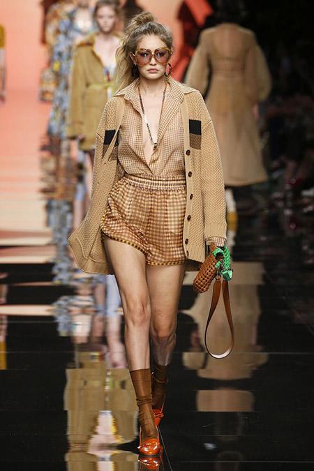 No desfile da Fendi da MFW Primavera / Verão 20, Gigi Hadid veste shorts bege xadrez, camisa e casacos bege.