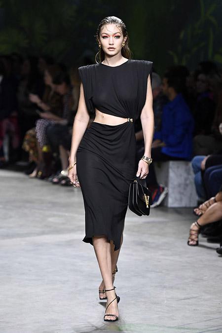 No desfile da Versace da MFW Primavera / Verão 20, Gigi Hadid veste vestido preto com recorte na cintura.