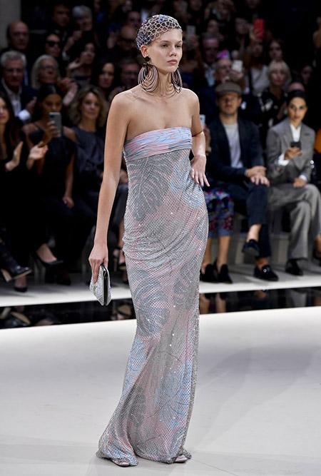 No desfile da Emporio Armani da MFW Primavera / Verão 20, modelo veste vestido longo tomara-que-caia, com estampa clara de folhas costela de adão; brincos grandes de círculo.