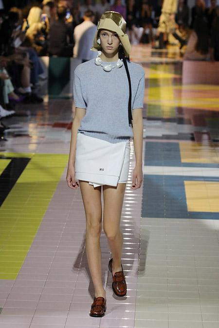 No desfile da Prada da MFW Primavera / Verão 20, modelo veste minissaia branca, mocassins marrons e suéter cinza.