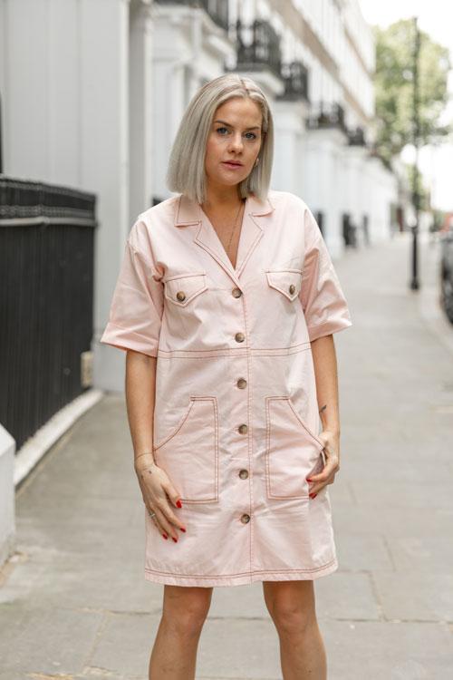 Eliza Rinaldi está vestindo um vestido rosa com botões e posa em pé com as pernas afastadas e mãos no bolso.