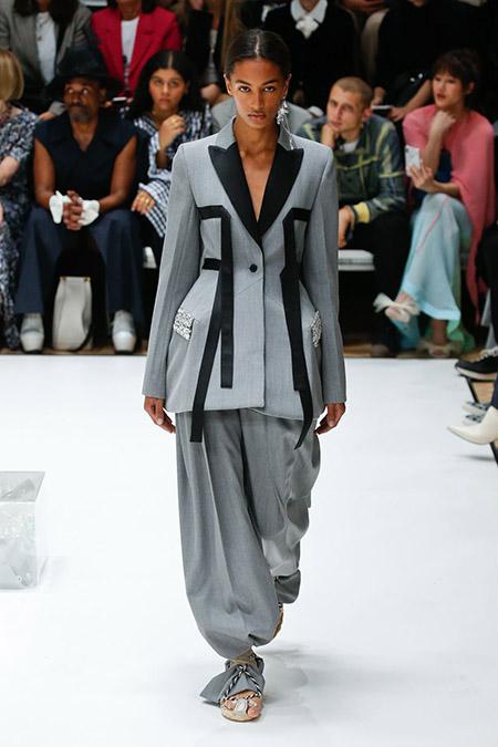 Desfile JW Anderson na LFW Primavera / Verão 20, modelo usa terno amplo em cinza claro com detalhes em preto.