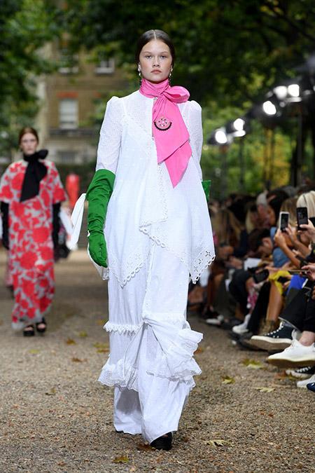 Desfile da Erdem na LFW Primavera / Verão 20, modelo veste vestido branco com lenço rosa no pescoço e luvas verdes.