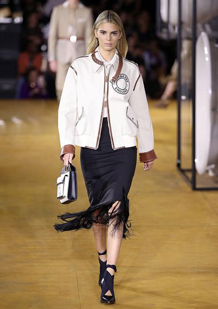 Desfile Burberry na LFW Primavera / Verão 20, Kendall Jenner veste casaco off white com punhos em couro marrom, saia preta midi com franjas e sapato bico fino com recortes.