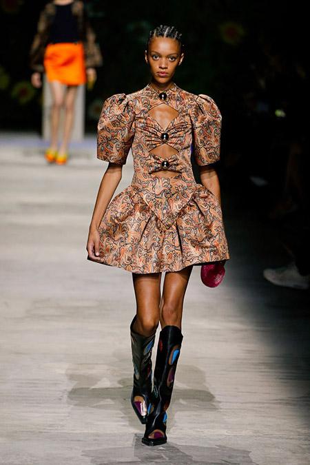 Desfile Christopher Kane na LFW Primavera / Verão 20, modelo usa vestido curto estampado em tons terrosos claros, recortes marcados por botões. Ela usa botas cowboy na altura dos joelhos.