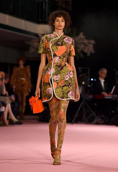 Desfile Richard Quinn na LFW Primavera / Verão 20, modelo usa vestido gola oriental e estampa floral em verde, lilás e laranja e meia calça na mesma estampa. Bolsa e sandália vermelhas.