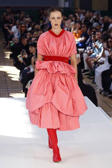 Desfile Molly Goddard na LFW Primavera / Verão 20, modelo veste vestido midi bufante rosa com gola e cinto vermelhos. Ela calça uma bota vermelha de cano alto.
