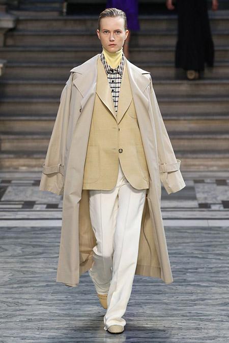 Desfile Victoria Beckham na LFW Primavera / Verão 20, modelo veste casaco bege, paletó bege mais escuro, camisa xadrez e calça branca. Por baixo da camisa, uma gola alta amarela pastel.