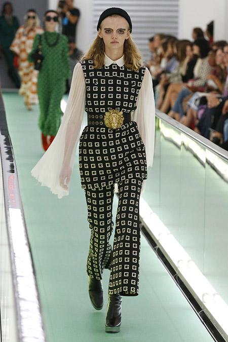 No desfile da Gucci da MFW Primavera / Verão 20, modelo veste conjunto em preto com o G da marca em branco e camisa de manga longa e esvoaçante.