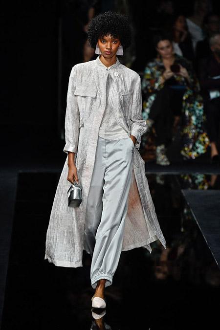 No desfile da Emporio Armani da MFW Primavera / Verão 20, modelo veste calça cinza clara, blusa e casaco sobretudo cinzas claro com textura.