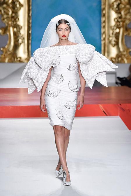 No desfile da Moschino da MFW Primavera / Verão 20, Bela Hadid é uma noiva com vestido curto, lábios vermelhos e mangas estruturadas.