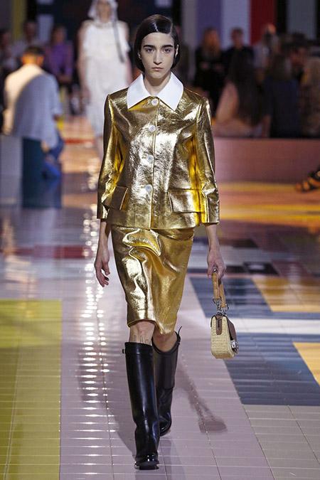 No desfile da Prada da MFW Primavera / Verão 20, modelo veste taieur dourado metálico e botas cano alto pretas.