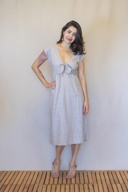 Modelo veste vestido midi bege com listras brancas verticais e uma estética minimalista.