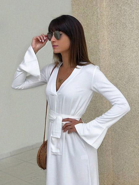 Modelo veste chemise branco de mangas longas, minimalista.