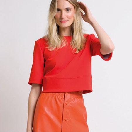Modelo loira sorrindo, veste moletom de manga curta vermelho e saia de courino laranja da marca D'Lolla