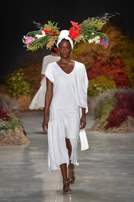 Modelo negra com turbante branco e flores na cabeça, desfila vestido branco mídi, no desfile de Issac Silva da SPFW N48.