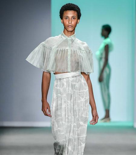Modelo negra de cabelos curtos desfila camisa cropped e saia longa brancos com estampa verde água, no desfile da Neriage da SPFW N48.