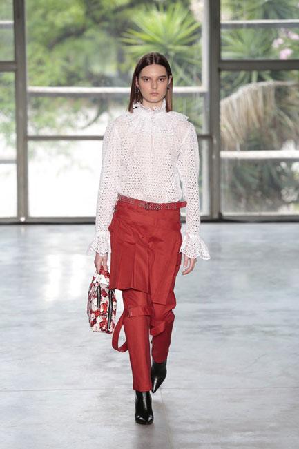 Modelo branca desfila camisa de laise branco e calça alfaiataria vermelha na passarela de Reinaldo Lourenço, na SPFW N48.