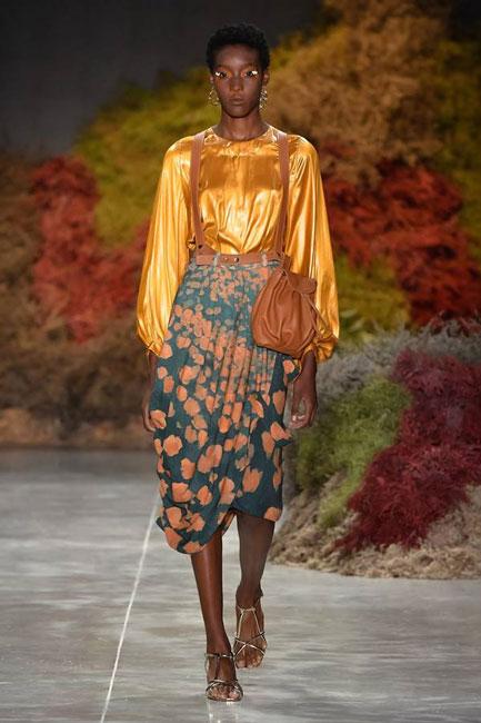 Modelo negra desfila blusa dourada e saia verde estampada e bolsa marrom, na passarela de Angela Brito, na SPFW N48.