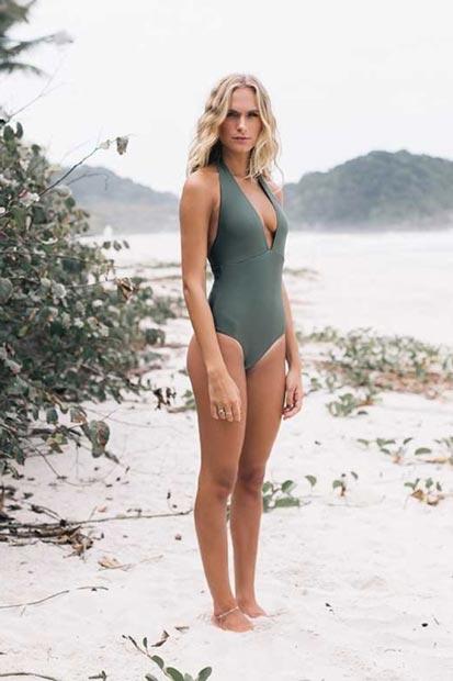 Modelo numa praia com folhas perto, posa em pé, usando maiô verde