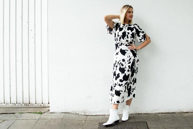 Eliza Rinaldi usa vestido midi com estampa de vaca, preto e branco e botas de cano baixo brancas. Ela está encostada em uma parede branca.