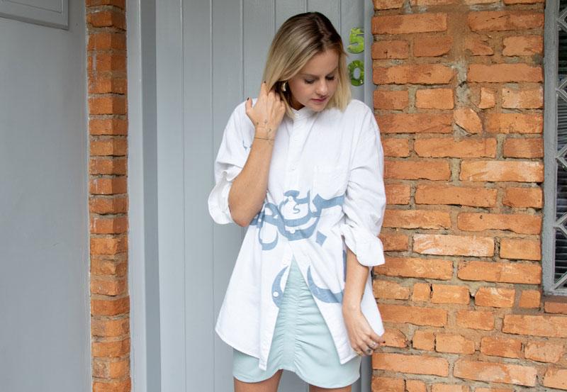 Eliza Rinaldi olha para baixo, está em frente a uma parede com tijolos com uma camisa branca, saia e uma bota branca.