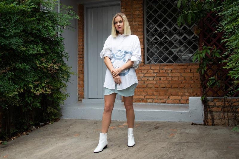 Eliza Rinaldi posa em frente a uma parede com tijolos com uma camisa branca, saia e uma bota branca.