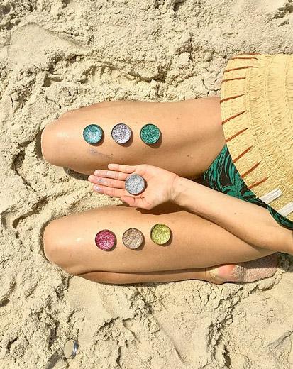 Modelo sentada na areia com embalagens de glitter biodegradável para o Carnaval, apoiadas nas pernas, nas cores verde, rosa, dourado, amarelo e prata
