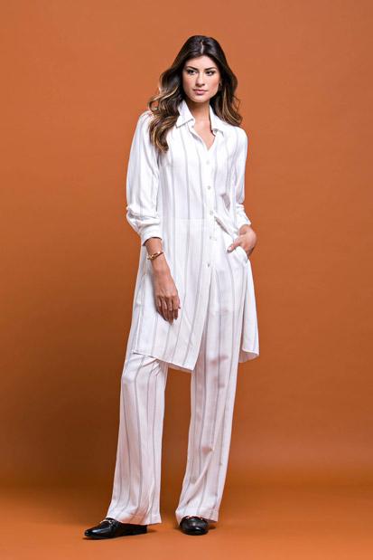 Modelo em pé, veste conjunto de calça e camisa longa brancos com listras cinza claras da marca Cleo Aidar