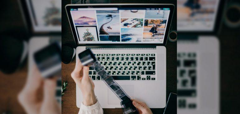 Mãos segurando filme em frente a um notebook