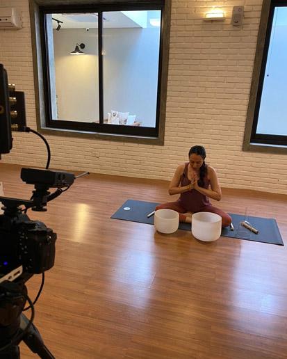 Instrutora de yoga com as mãos unidas em frente às tigelas de cristal e em frente às câmeras.