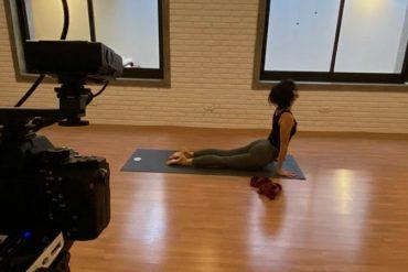 Mulher faz posição de yoga em frente à câmeras de vídeo