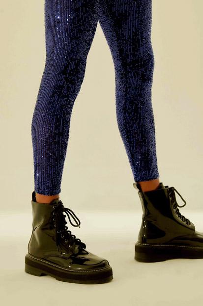 Pernas da modelo vestindo uma calça de paetês azul e calçando as botas pretas de verniz.