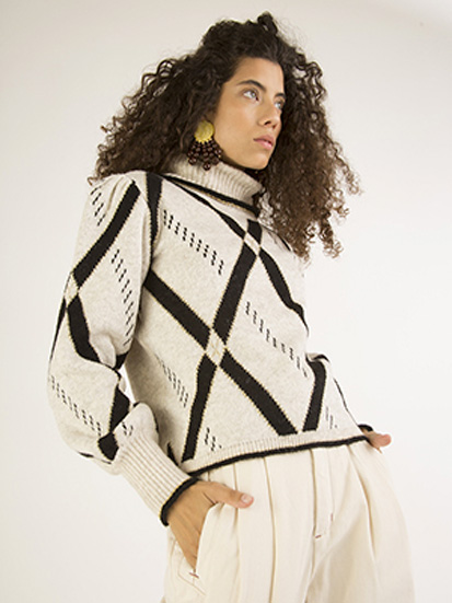Mulher veste o blusão de tricô, que é branco e tem losangos grandes pretos.